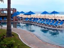 Piscina con los paraguas y la playa azules de los recliners Fotos de archivo libres de regalías