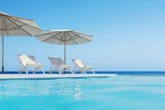 Piscina con tres sillas de cubierta, paraguas Fotografía de archivo