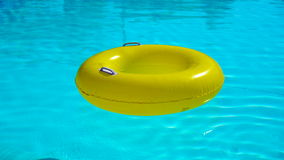 Piscina con un anello gonfiabile brillantemente giallo stock footage