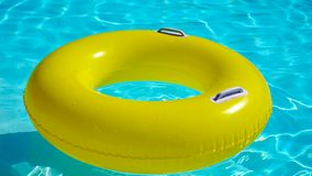 Piscina con un anillo inflable brillantemente amarillo metrajes