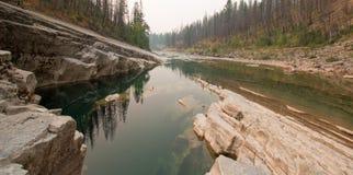 Piscina de color verde oscuro del agua inmóvil en la garganta de la cala del prado en el área de Bob Marshall Wilderness en Monta Foto de archivo libre de regalías