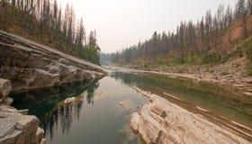 Piscina de color verde oscuro del agua inmóvil en la garganta de la cala del prado en el área de Bob Marshall Wilderness en Monta Fotos de archivo libres de regalías