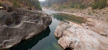 Piscina de color verde oscuro del agua inmóvil en la garganta de la cala del prado en el área de Bob Marshall Wilderness en Monta Fotografía de archivo