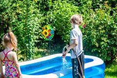 Piscina de enchimento do rapaz pequeno e da menina com água imagem de stock royalty free