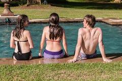 Piscina de la nadada de las muchachas del muchacho que se relaja Fotografía de archivo