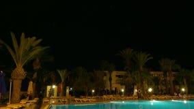 Piscina de la noche con la iluminación y palmeras en lapso de tiempo de lujo almacen de video