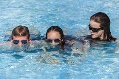 Piscina de las gafas de sol del muchacho de las muchachas Imagen de archivo