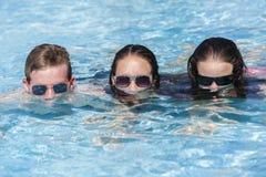 Piscina de las gafas de sol del muchacho de las muchachas Imágenes de archivo libres de regalías