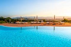 Piscina de lujo hermosa con agua azul, los paraguas y los sunbeds brillantes en paisaje toscano Puesta del sol del verano de la t Fotos de archivo libres de regalías