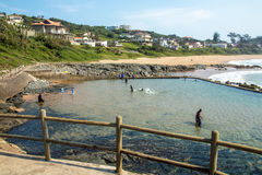 Piscina de marea contra la playa y solares residenciales costeros Imágenes de archivo libres de regalías