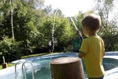 Piscina de relleno del muchacho con agua imagen de archivo
