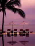 Piscina del horizonte en el océano, los ociosos del sol y las sombrillas Foto de archivo libre de regalías