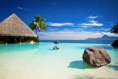 Piscina del infinito con la playa y el océano artificiales Imágenes de archivo libres de regalías