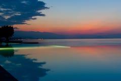 Piscina del infinito en la playa en la puesta del sol Imágenes de archivo libres de regalías