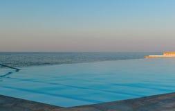 Piscina del infinito en la playa en la puesta del sol Imagen de archivo libre de regalías