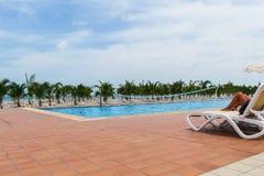 Piscina delante de una playa en el Caribe con las palmeras y el cielo azul fotos de archivo