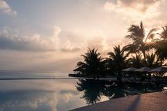 Piscina e céu maravilhosos do por do sol Paisagem tropical luxuoso da praia, cadeiras de plataforma e vadios e reflexão da água e imagens de stock