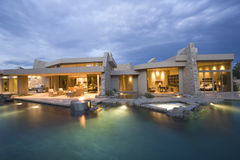 Piscina e casa moderna iluminada fotos de stock royalty free