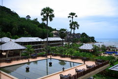 Piscina en la opinión del mar, ociosos del sol al lado del jardín y edificios y pagoda Fotos de archivo libres de regalías