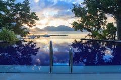 Piscina en la playa tropical en la puesta del sol Imagenes de archivo