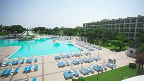 Piscina en un día asoleado vídeo Hermosas vistas de los jardines tropicales, del sundeck del hotel y de la piscina metrajes