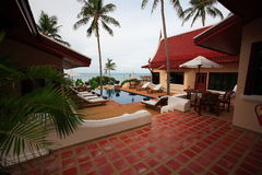 A piscina entre o bungalow, vadios do sol no mar na areia encalha foto de stock