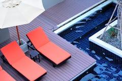 Piscina laterale arancio delle sedie di spiaggia Fotografia Stock
