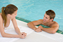 Piscina - le coppie felici chiacchierano sul poolside immagini stock