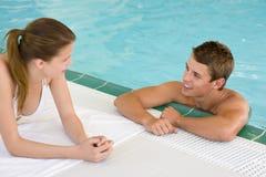 Piscina - los pares felices charlan en poolside Imagenes de archivo