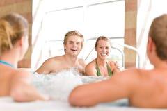 Piscina - los pares felices se relajan en tina caliente Imagenes de archivo