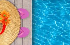 Piscina, piattaforma di legno e scarpe rosa della spiaggia con il cappello Fotografia Stock