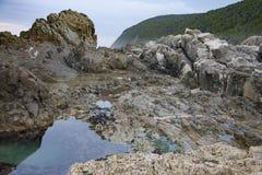 Piscina rocosa durante la bajamar en la reserva de naturaleza de Tsitsikamma cerca de la boca de río de las tormentas en Suráfric Imágenes de archivo libres de regalías