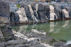 Piscina rocosa durante la bajamar en la reserva de naturaleza de Tsitsikamma cerca de la boca de río de las tormentas en Suráfric Fotos de archivo libres de regalías