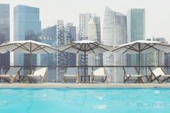 Piscina, sillas de cubierta, paraguas, ciudad, delantera Fotografía de archivo libre de regalías