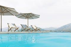 Piscina, sillas de cubierta, paraguas, montañas Foto de archivo libre de regalías