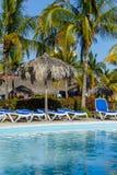 Piscina, sillas del sol y palmeras en todo el hotel inclusivo fotografía de archivo libre de regalías