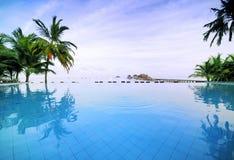 Piscina sin borde con el mejor tropical romántico imagen de archivo libre de regalías