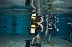 Piscina subacuática con los zambullidores de equipo de submarinismo Fotos de archivo