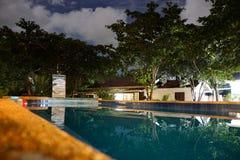 Piscina tropical de la noche con reflexiones fotos de archivo libres de regalías
