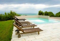 Piscina vacía con las camas de madera del sol y vista al mar Imagen de archivo libre de regalías