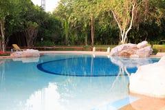 Piscina, vadios do sol ao lado do jardim e construções fotografia de stock royalty free
