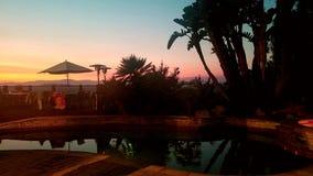 Piscina y cubierta del patio trasero en la puesta del sol Imagen de archivo