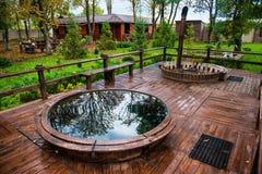 Piscina y Jacuzzi de la sauna con la zona de recreo del resto al aire libre en chalet de lujo del bosque Foto de archivo libre de regalías