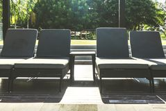 Piscina y puesta del sol lateral de las sillas de playa Fotografía de archivo libre de regalías