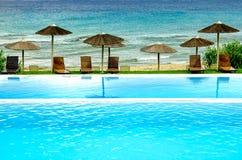 Piscina y sunbeds de lujo con vista al mar Imagen de archivo libre de regalías