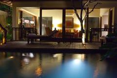 Piscina y terraza de la noche para el resto detrás Foto de archivo