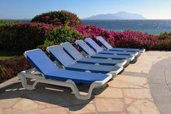 Piscine avec des lits du soleil Photographie stock libre de droits