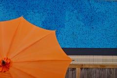 Piscine avec le parapluie orange photographie stock libre de droits