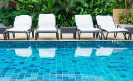Piscine avec les chaises de plage blanches Images libres de droits