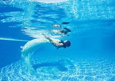 Piscine bleue de jour ensoleillé de beau de femme de fille de robe bain sous-marin blanc de plongée Photographie stock